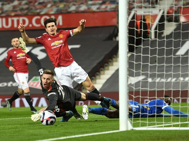 Harry Maguire and Danny Welbeck collide in the box during the second half at Old Trafford